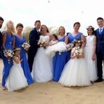 photo of weddi gbgroup, bride in white and bridesmaids in sky blue, groomsmen in grresy all standi ng on the beach in Camber Sands
