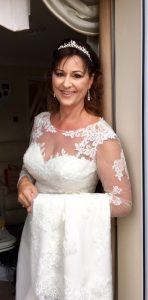 Photo of bride leaning oon doorframe, she is smiling and wearing a white lace dress
