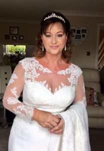 Photo of bride in white dreaa with her train over her arm. Dress has lace sleeves and topof bodice, bride has light brown long hair