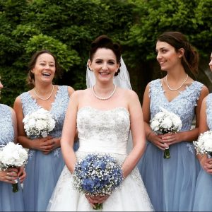 Photo of smiling bride in white dress with veil and golding blue bouquet. @ bridesmaids are seen fully and 2 others partially, all wearing blue