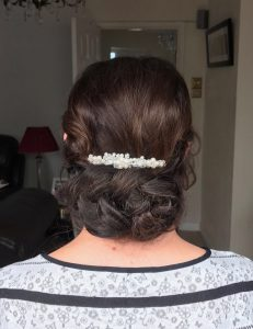 photo of back of client's head, brown hair in updo with white pearl hairclip