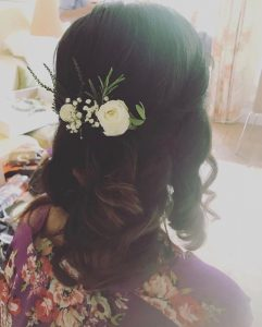 photo of back of brunette bridesmaid's he]air, long curls and a white flower detail