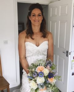 Photo of bride with long pale brown hair holding bouquet of summer flowers