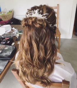 photo of back of bride's weddi g hair , long pale browm=n hair half ip half down with white pearliised hair clip