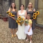 Bride wesring ivory dress and her bridesmaids in grey ( 2 older bridesmaids ) and flowers girl wearing white and yellow dress. All holding sunflowers