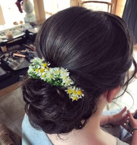photo of back of brides hair, brunette updo with wild flowers in