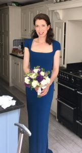 Full lenght photo of brunette bride in blue dress, hildi g bouquet and smiling