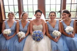 Bride and bridesmaids sitting down, Bride in white with blue bouquet, bridesmaids in bLue with white bouquets