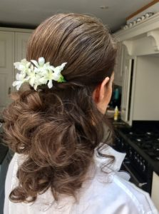Close up photo of long broen haired bride, the back of her hair has a white flower