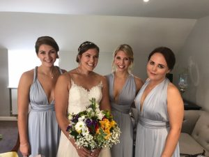 photo of 3 adult bridesmaida in grey dresses and bride in white she is holding colourful bouquet