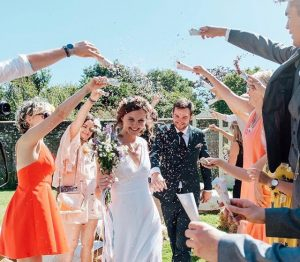 photo of a summer wedding, guests throwing confetti over bride and groom