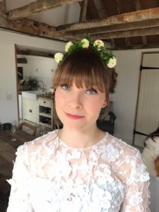 close ip photo of [pretty smiling brunette bride, hair in french palits with flowers