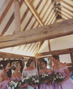 Photo of bride dressing in white and 4 adukt bridesmiafs in pink, inside a barn
