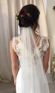 photo of back of bride to be, wearing white wedding dress, veil , brunette hair with flowers