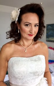 photo of brunette bride with white dress, vintage hairstyle , flower in hair and red lipstic