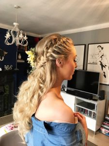 head & shoulders image of blonde, long hair, loose and curly with french pleat and flowers
