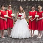 photo of bride wearing white and 4 bridesmaids in scarlet
