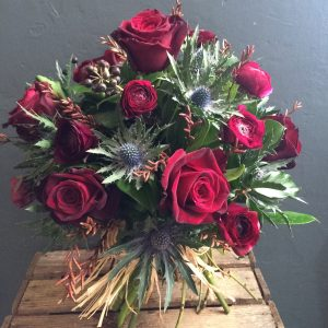 photo of bouquet of dark red roses and thistles