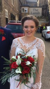 photo of bride wearing white lace dress , smiling holding bouquet